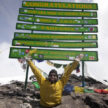 Spencer West at the summit of Mount Kilimanjaro